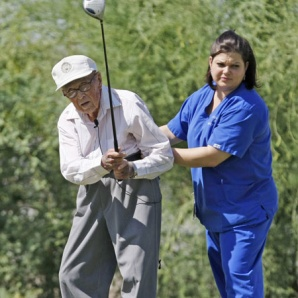 Edwin Dibos, age 104, hits his drive on the 3rd tee box with some help from hospice nurse Nicole Phillips (right) at Encanto Nine Golf Course / Rob Schumacher/The Arizona Republic